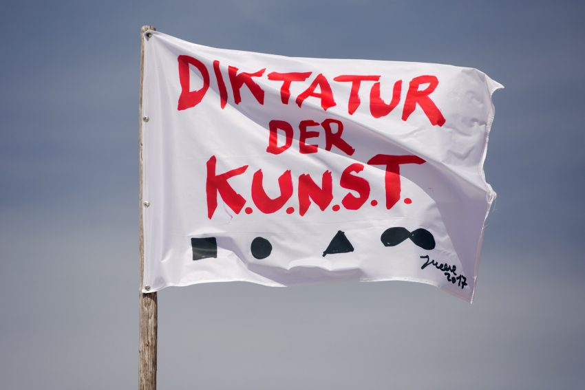 "<p style=""text-align: center;""><span style=""font-size: 8pt;"">Jonathan Meese, Diktatur der Kunst (2017), CMYK print on flag fabric, 106 x 150 cm, Kunstverein Amrum, 2017. Photo: Sandra Hermannsen</span></p>"